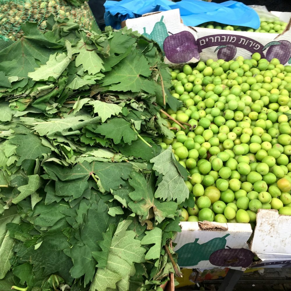 Vine leaves and sour spring plums - for cooking not eating - at Jerusalem's Mahane Yehuda Market.