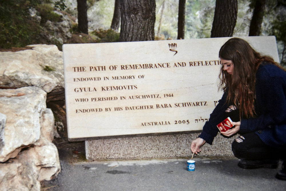 Baba's grand-daughter Delilah Schwartz lights a candle on the path of remembrance, which Baba endowed in memory of her father at Yad Vashem, the Holocaust Memorial in Jerusalem.