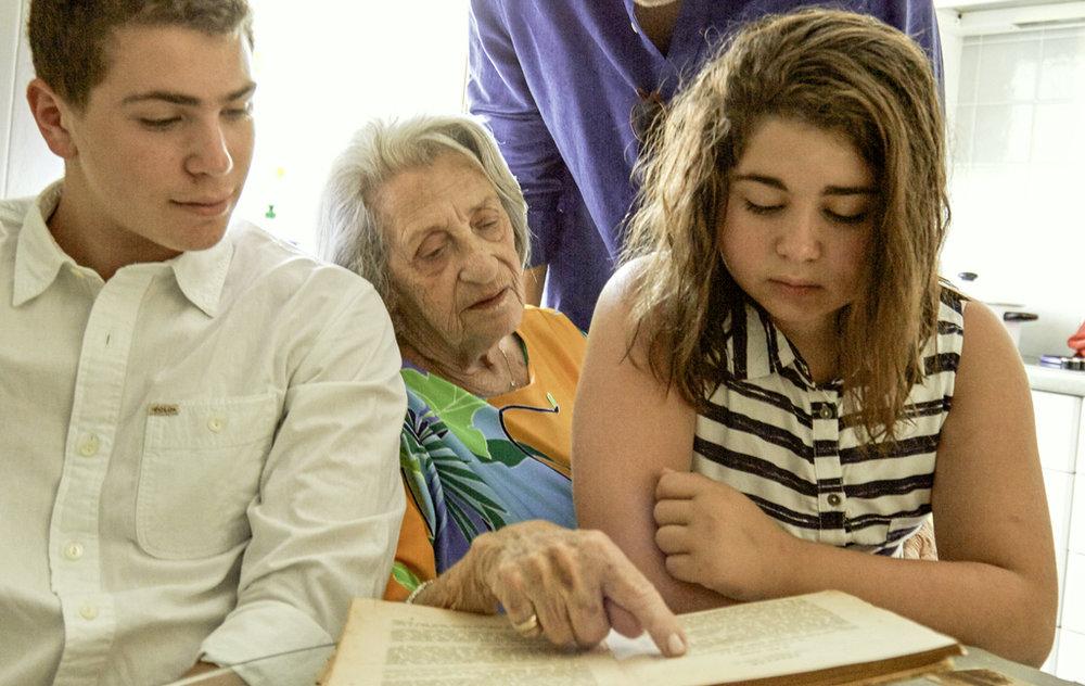 Agi Adler showing her grandchildren her old recipe books.