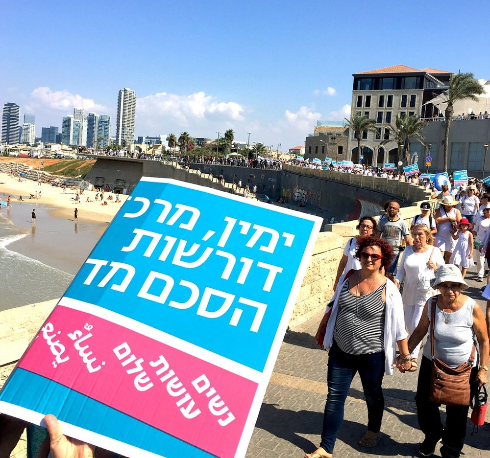 "The poster reads 'Right, Centre and Left demand a poltiical agreement"". Women Wage Peace is written in Arabic and Hebrew."