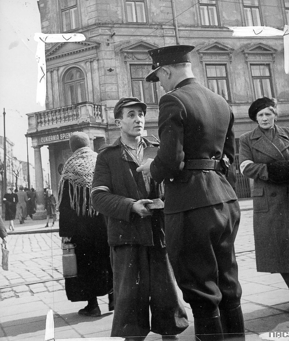 Polish police officer checks Jewish man's documents, Krakow Ghetto, 1941. (Polish National Archive)