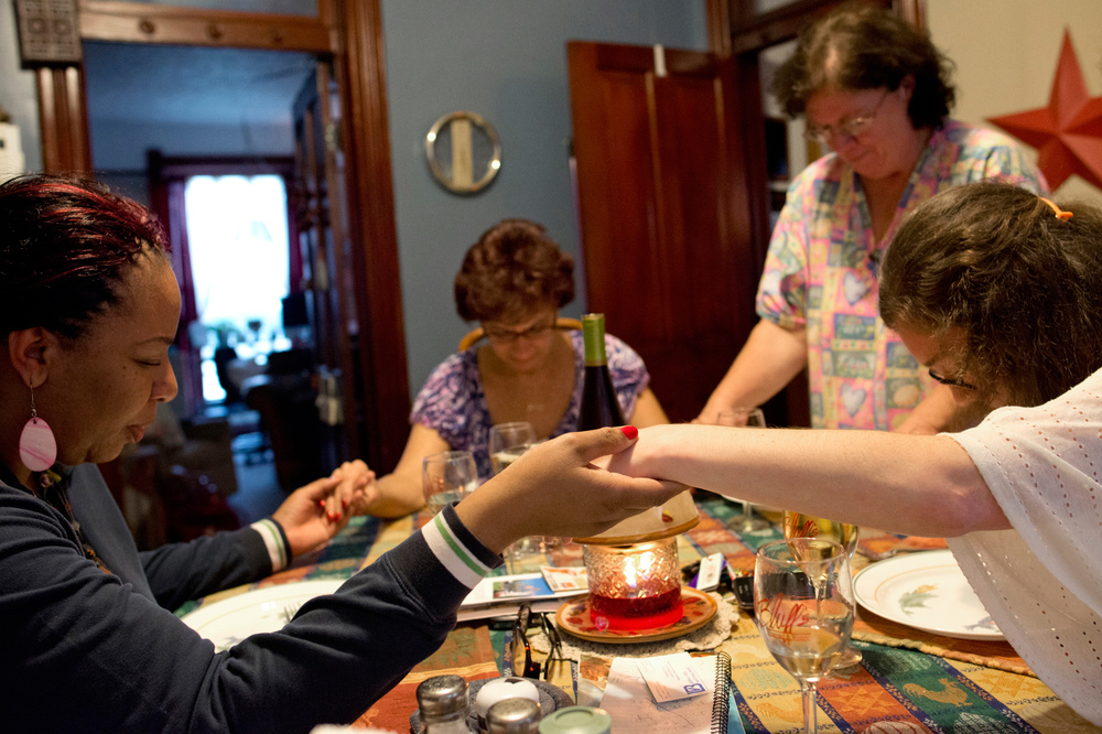 Debra Kennedy, left, Gayle Ayala, middle left, Sheryl Moore, middle right, and Kellie hold hands in prayer before sharing a meal at the Hospitality House. Kellie and Sheryl both have husbands staying at Menard Correctional Center in Chester, Ill.