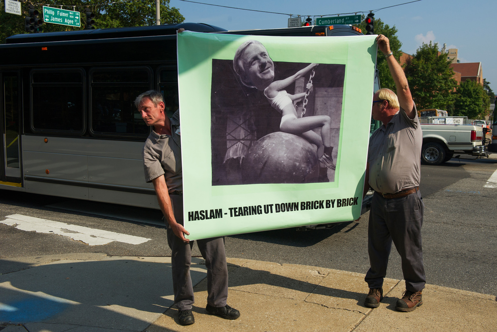 "University zone maintenance workers Cecil Woody and Donnie Lowery hold up a banner depicting Gov. Haslam on the body of Miley Cyrus from her music video for the song ""Wrecking Ball"" during a rally by UT employees and supporters who are concerned about Gov. Bill Haslam's plan to privatize management and operations of virtually every state-owned facility, including colleges and universities on Cumberland Avenue Thursday, Sep. 3, 2015. ""We need people to understand that it is not just university employers this is affecting, it is the community too, "" Woody said."