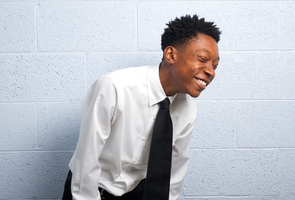 Jaden Stone of the L&N S.T.E.M. Academy bursts into a laugh and attempts to not smile with his teeth while posing for a portrait as a new member of the National Achievers Society at the Greater Warner Tabernacle Church Saturday, Sept. 19, 2015.