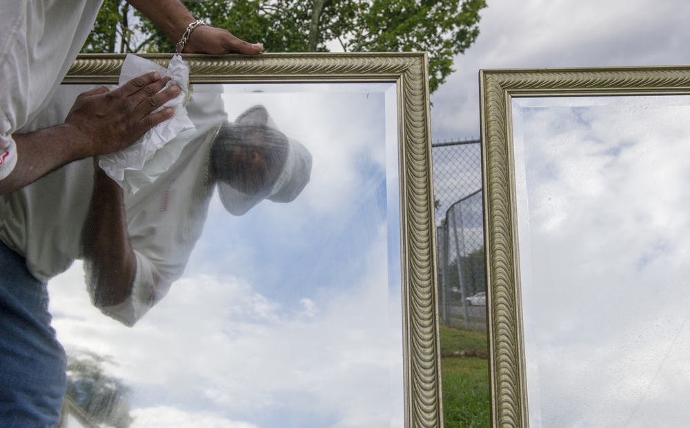 "Roland Douglas of Knoxville cleans a display of mirrors in the front year of his home Saturday, Sep. 26, 2015. Douglas works as a craftsman out of his home whose attitude is ""No job too small"". He said he has also been making silver jewelry for a twenty years, a trade that he learned from his father."