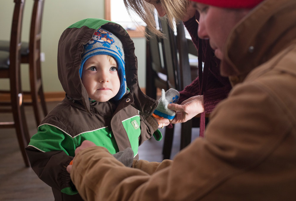 Travis helping Zach with his gloves before his first sledding experience.