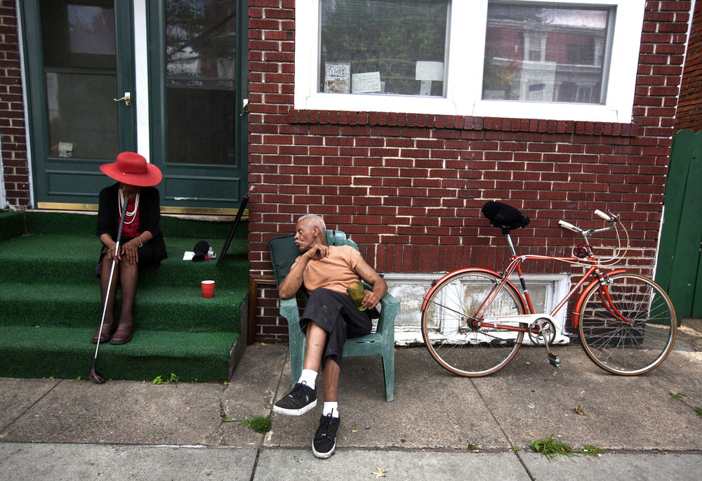 Esther Edwards, 83, sits on her front step while waiting for the police to pick up an intoxicated man who fell off of his bike in front of her home in Harrisburg, Penn. Edwards can often be seen dressed to impress with a golf club in hand, that she keeps with her for protection, while keeping an eye on the neighborhood. She said she recently moved back to Harrisburg after a long career as a journalist, a model instructor, and the first African American Budweiser model.