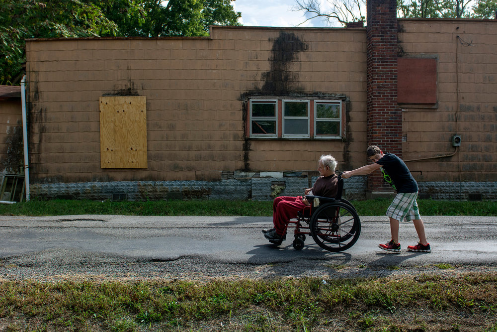 Chico Bordoy, 13, pushes his father Ramone Bordoy, 72, to their home in Muddy, IL where they live with Chico's adult sister and brother, with special needs. Ramone said he lived in Muddy when he was younger and moved back along with his children so that they could help to take care of him. Lori, his daughter, said he is suffering from renal failure and requires a lot of care from her and Chico.
