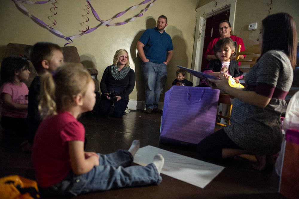 "Erickia Wilson (center left) and her husband Michael Wilson (center right) watch as Angelica, the birthmother of the child they will adopt, helps her daughter Prisilla, 3, open presents at her birthday party at Angelica's home in Evansville Friday Oct. 24, 2014. Erickia said for her and Michael this experience is about more than their baby, it is about two families becoming one,""We have fallen in love with all of them as a whole.""  Michael and Erickia Wilson have been trying to have children for seven years. In May, after six miscarriages, one failed adoption and a lot of heart break they met Angelica, a mother of two who was not financially prepared to take care of the baby she was carrying. After meeting once, Angelica agreed to place her baby in an open-adoption in the Wilson's home. The couple decided to try one more time to parent a child."