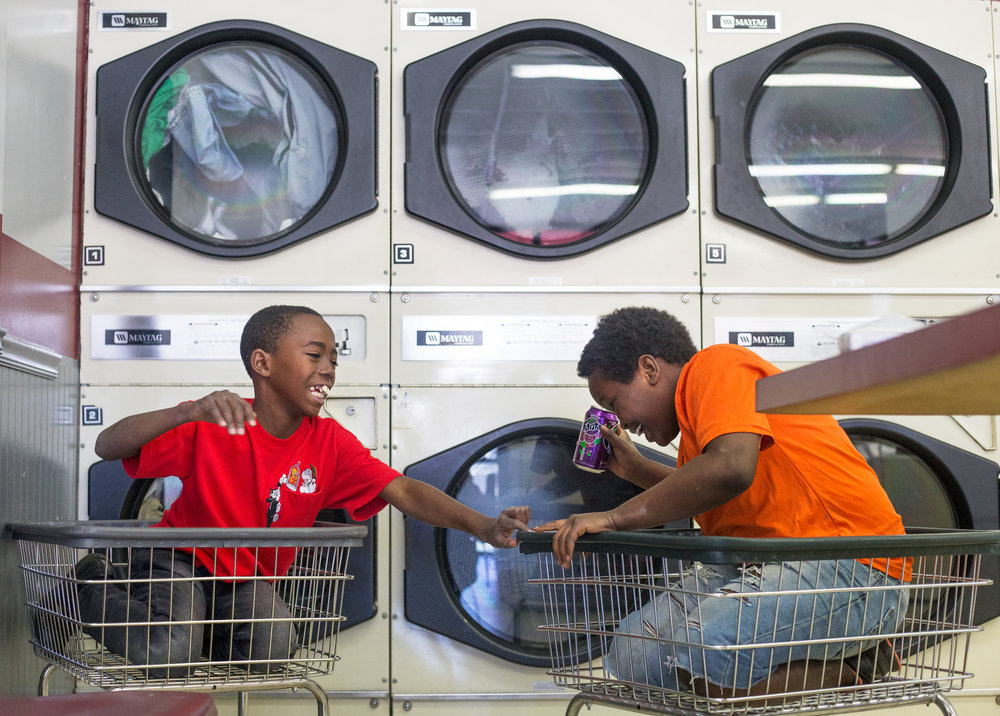 Mohammed Kamara, 11, left, and Joseph Uwiz, 12, play in the laundry carts at Super Wash House in North Knoxville, April 5, 2017.