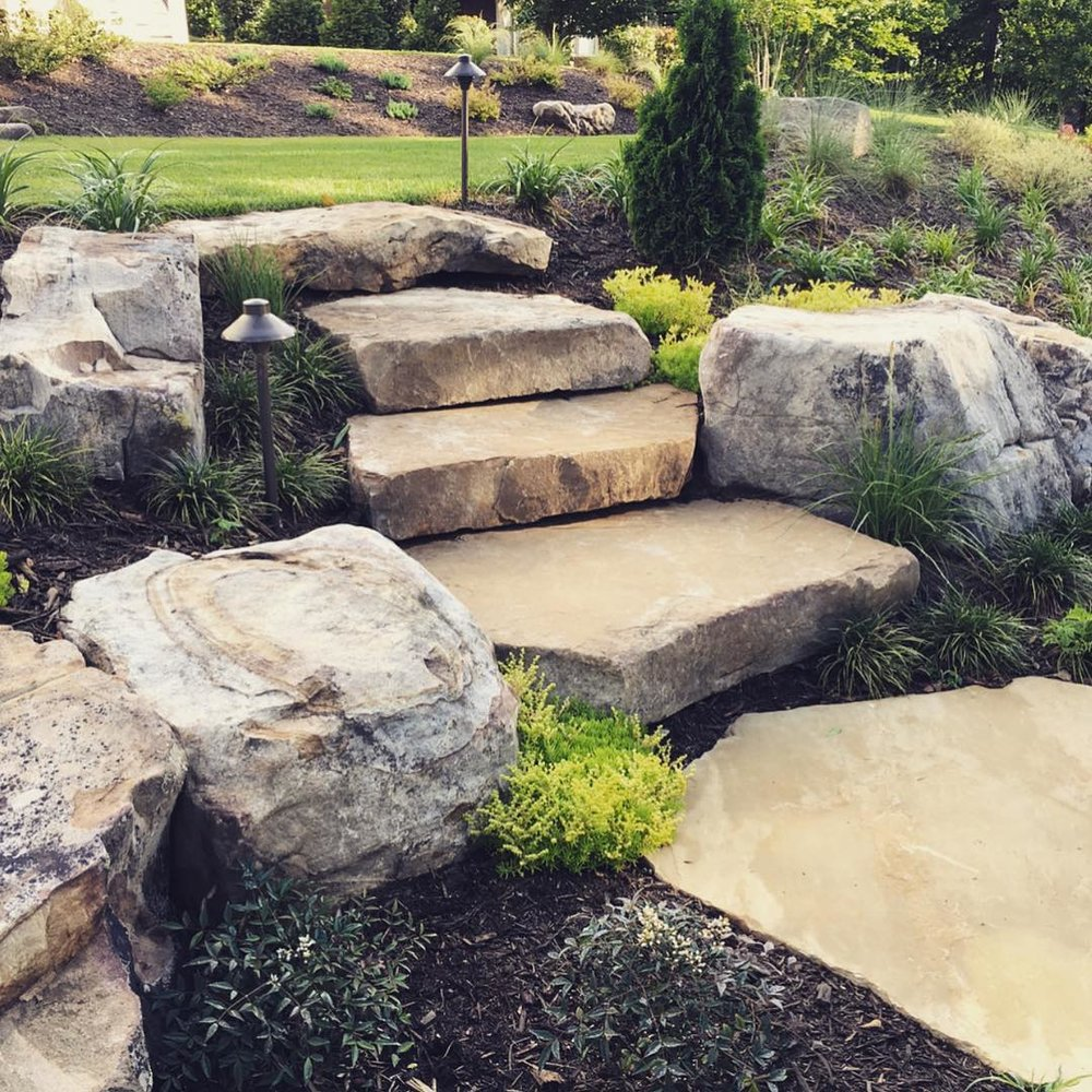 Rock steps, mulchbeds and lighting create a unique outdoor landscape space