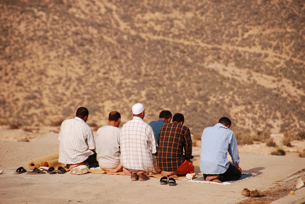 Muslim men praying toward Mecca