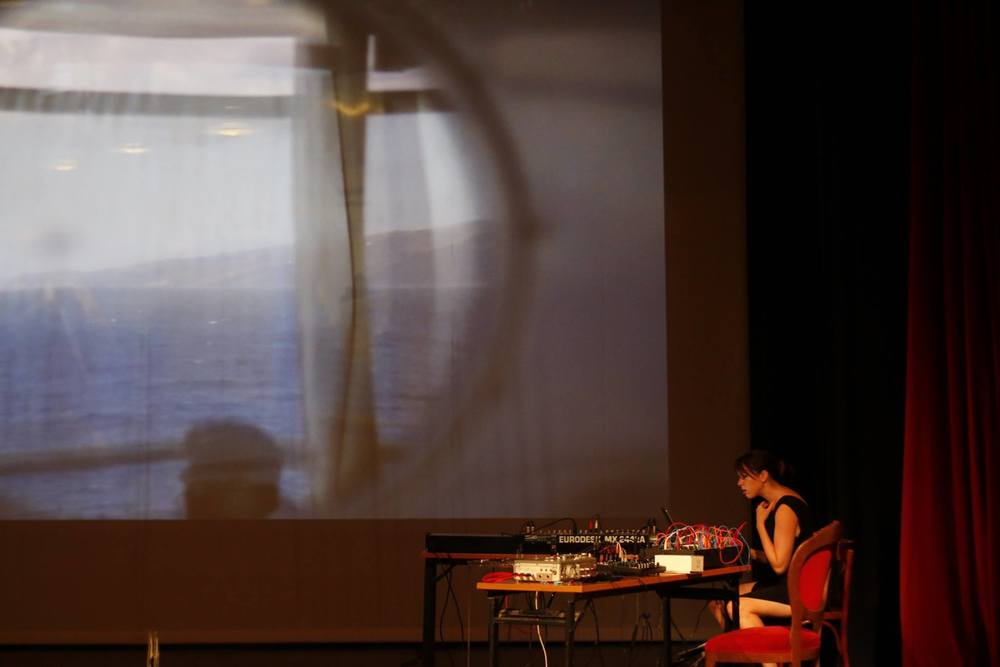 "Somewhere, Anywhere, Nowhere (image from Apollon Theatre Syros Screening) HD Video/Projections/Live Soundtrack/12min21 (2015) (link to soundtrack) Camera: John Schmidt Sound: Alyssa Moxley ""Somewhere, Anywhere, Nowhere"" includes images, filmed projections, and sound recorded on the ferry, in the dock, the Eastern Telegraph Company, and the former quarantine building in the Lazaretto area of Syros. Created during the Syros Sound Meetings/Syros International Film Festival Residency."