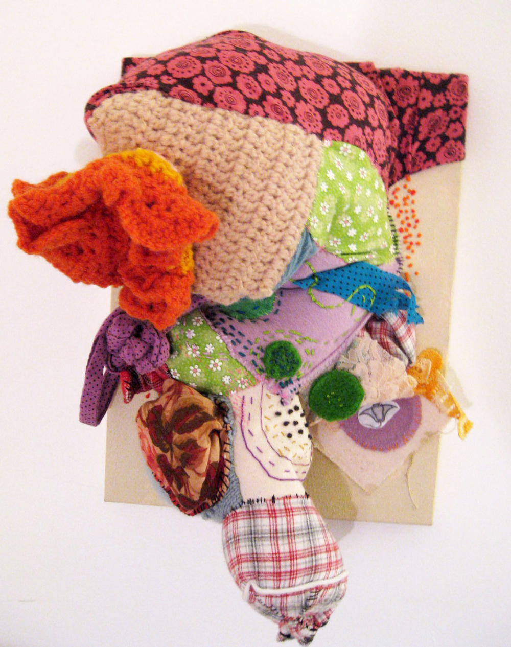 "The Soft Sting,  2010. Fabric, yarn, clothing, felt, paper, thread, embroidery floss, fiberfill, acrylic on canvas. 15""    x 10.5 ""    x 7.5 "". Courtesy of the artist."