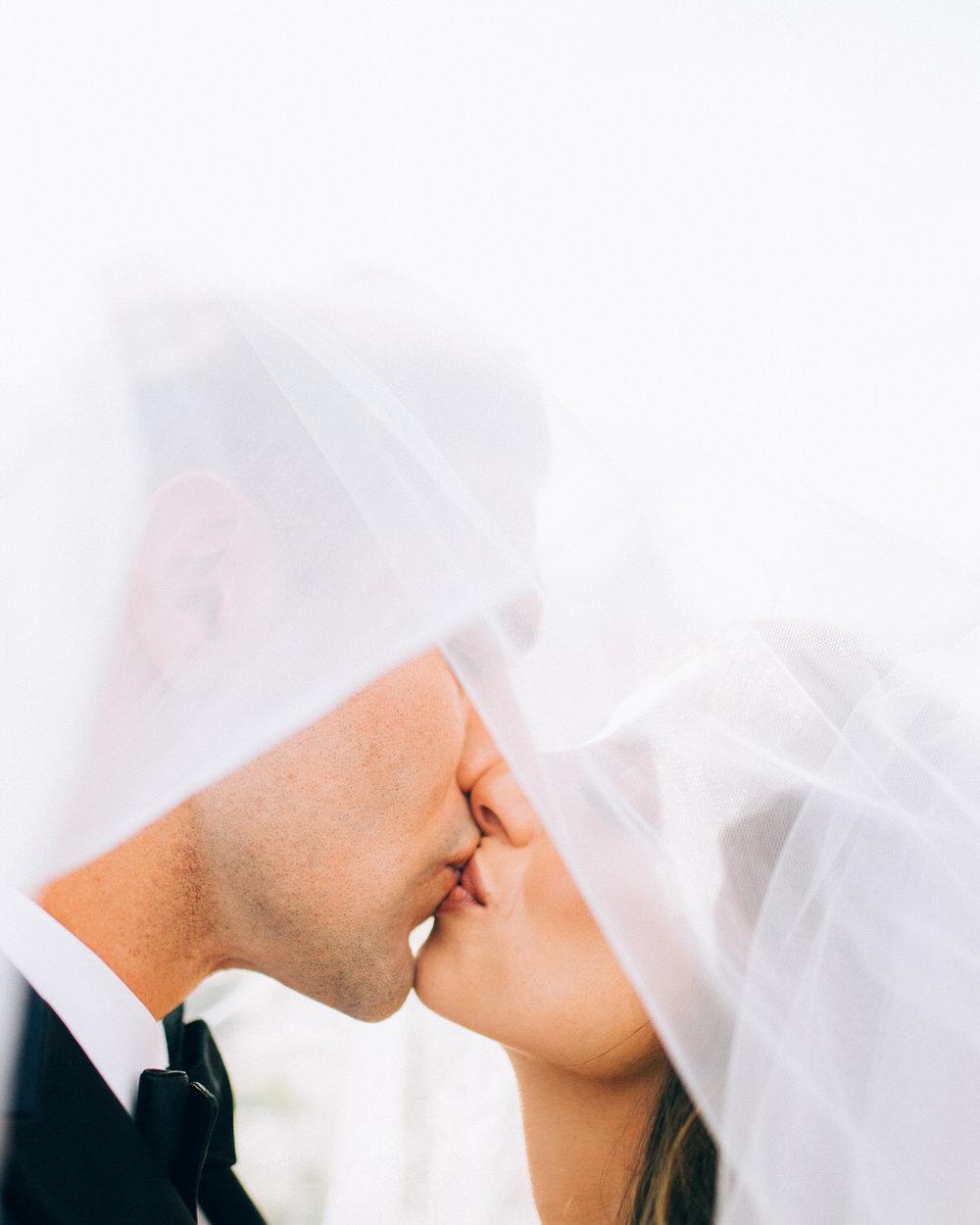 Bride and Groom Kissing under veil Armature Works Tampa
