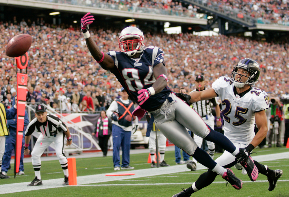 New England Patriots wide receiver Deion Branch reaches for a ball in the endzone while under pressure by Baltimore Raves cornerback Chris Carr in the fourth quarter at Gillette Stadium in Foxboro, Massachusetts on October 17, 2010. The Patriots defeated the Ravens 23-20 in overtime.