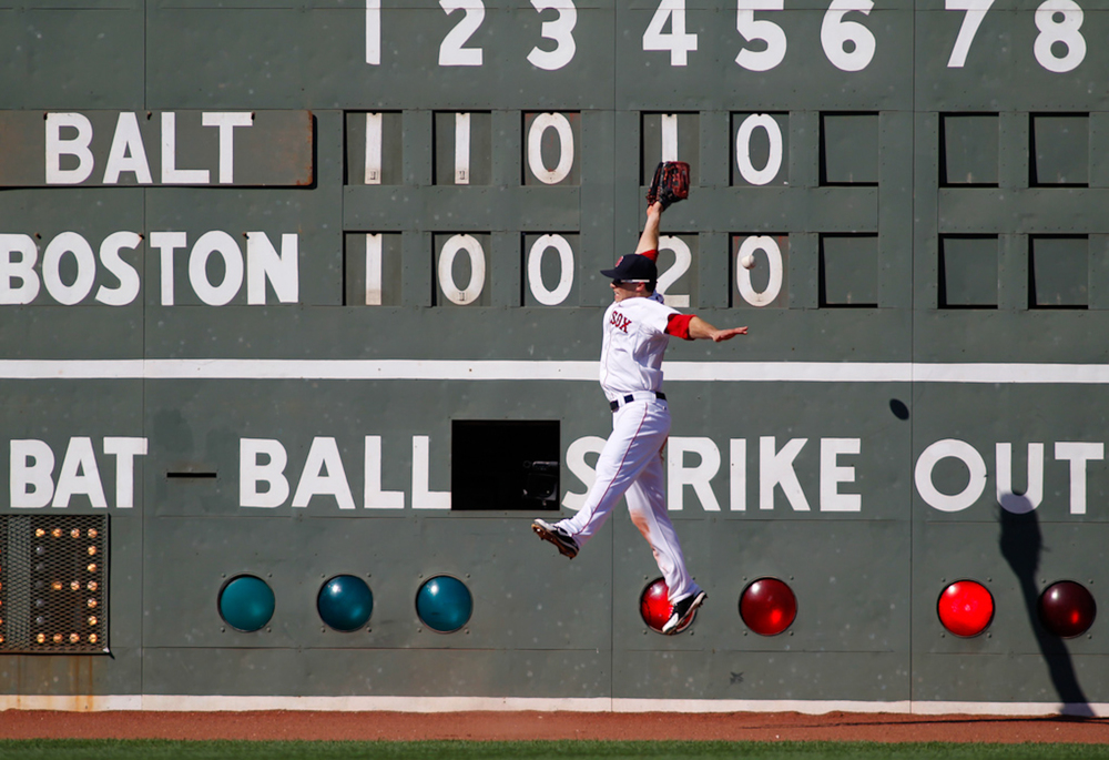 Boston Red Sox left fielder Daniel Nava leaps for a double hit by Baltimore Orioles batter Manny Machado in the sixth inning at Fenway Park in Boston on Saturday, September 22, 2012.