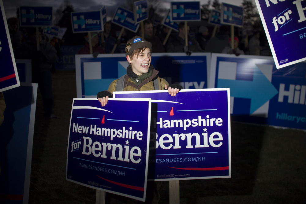 Eliza Walp of Chestertown, New York who works for the campaign for Democratic candidate for president Bernie Sanders, chants in support of Sanders while surrounded by Hillary Clinton supporters prior to a Democratic debate at St. Anselm College in Manchester, New Hampshire on December 19, 2015. This will be the third Democratic debate.