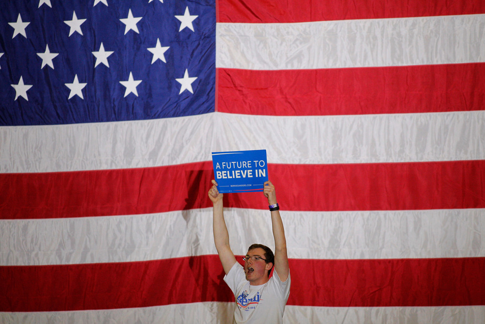 A supporter of Democratic presidential candidate Bernie Sanders, holds up a sign while waiting for the candidate to arrive at a Super Tuesday rally at the Champlain Valley Exposition in Essex Junction, Vermont on March 1, 2016.
