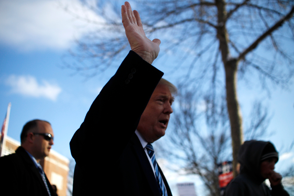 Republican presidential candidate Donald Trump waves to the crowd as he walks back to his motorcade after a visit to the primary polling station at the Webster Elementary School in Manchester, New Hampshire on February 9, 2016. The New Hampshire presidential primary is the first in the nation and is the culmination of months of campaigning by a large field of presidential candidates.
