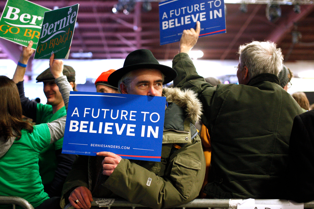 David Rosane, of Paris, holds a sign in support of Democratic presidential candidate Bernie Sanders, while waiting for the candidate to arrive for a Super Tuesday rally at the Champlain Valley Exposition in Essex Junction, Vermont on March 1, 2016. Rosane cast an absentee ballot from Paris but flew back to Vermont recently to attend the rally.