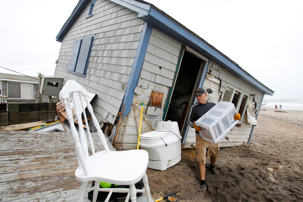 Pete Duhamel of South Kingstown, Rhode Island helps a friend (not pictued) remove his personal items from his cottage after it was damaged by Hurricane Sandy storm surge at Roy Carpenter Beach in South Kingstown, Rhode Island on October 30, 2012.   The area was one of the hardest hit by the storm surge from Hurricane Sandy.