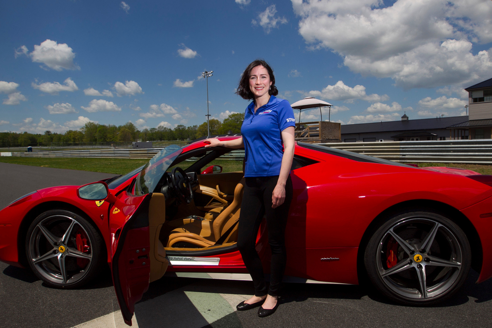 Race car driver Theresa Condict poses for a photo on the track at the Thompson Speedway with a 2012 Ferrari 458 Italia in Thompson, Connecticut on May 23, 2016. Condict competes in the Sports Car Club of America Improved Touring R class and also works at the Speedway which uses the Ferrari for it's exotic car experience.