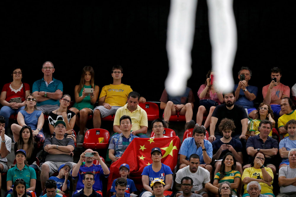 Members of the audience look on as China's Gao Lei competes in the qualifying round of Men's Trampoline Gymnastics in the Rio Olympic Stadium at the 2016 Rio Summer Olympics in Rio de Janeiro, Brazil, on August 13, 2016.