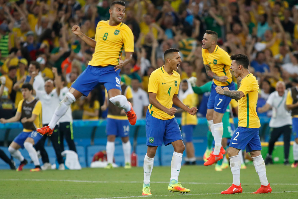 Brazil players celebrate after a save by their goaltender during an overtime shoot-out against Germany in the Men's Gold Medal soccer match at the 2016 Rio Summer Olympics in Rio de Janeiro, Brazil, on August 20, 2016. Brazil defeated Germany in 5-4 in overtime penalty kicks.
