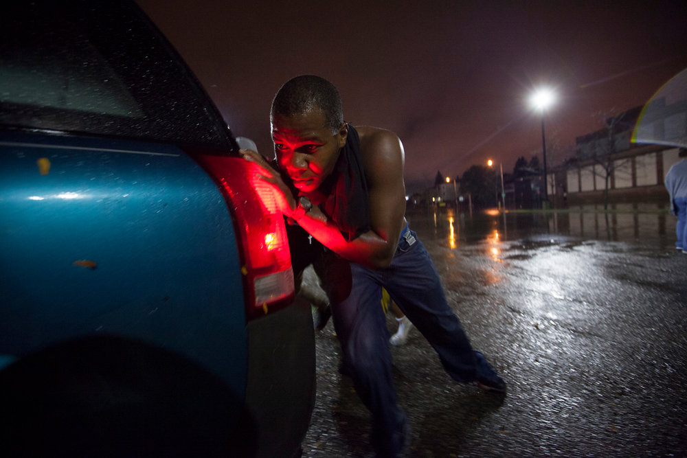 Good Samaritan Elijah Armstrong of Worcester helps push a strangers car out of flood waters on Washington Street and into a nearby Burger King parking lot in Worcester, Massachusetts on October 21, 2016. Flash flooding in the area left many motorists stranded and closed down parts of route I-290.