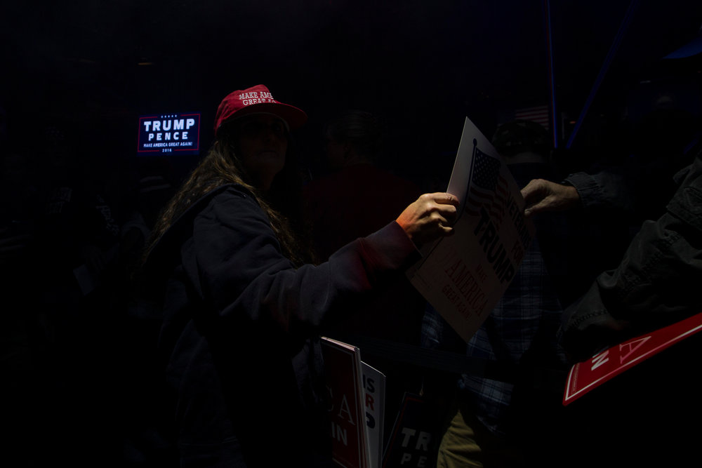 A volunteer for Republican presidential nominee Donald Trump hands out signs before the candidates arrival for a rally at the SNHU Arena in Manchester, New Hampshire on November 7, 2016.