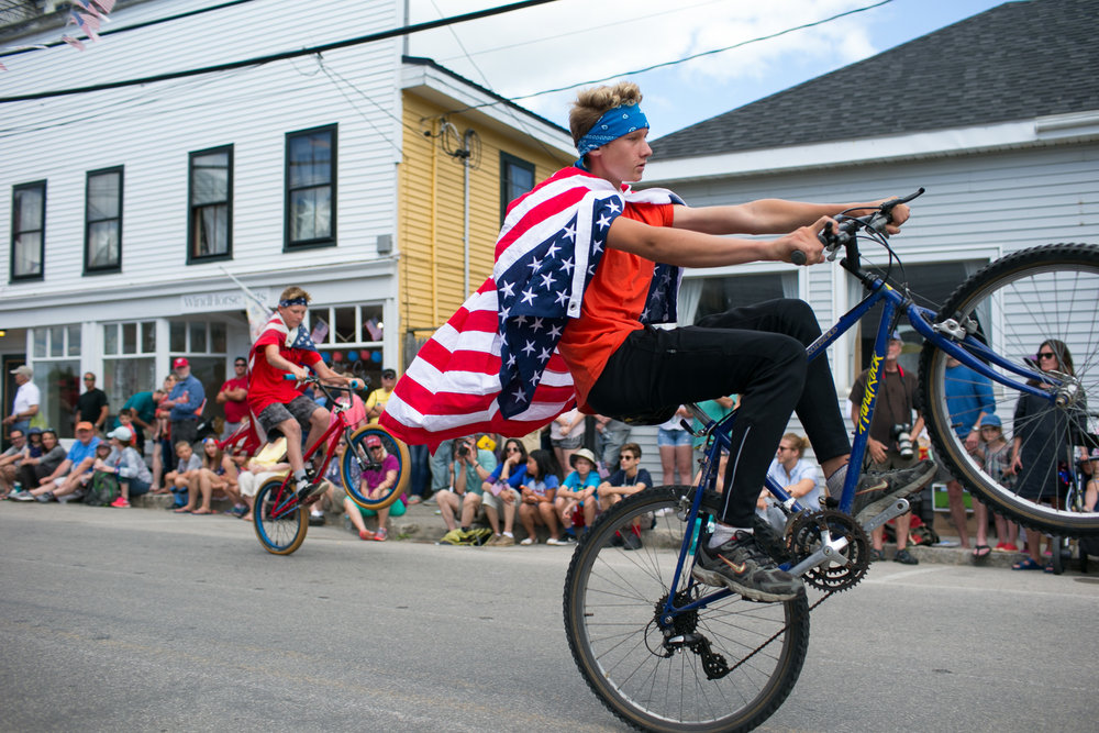 A group of boys on bicycles make their way down Main Street during the Independence Day Parade on the island town of Vinalhaven, Maine on July 4, 2017.