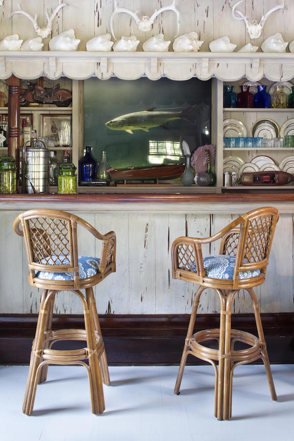 Lizzie Pulizer, daughter of Lilly, puts a bohemian spin on her mother's interior decorating aesthetic with rattan bar stools and a beachy distressed driftwood bar.