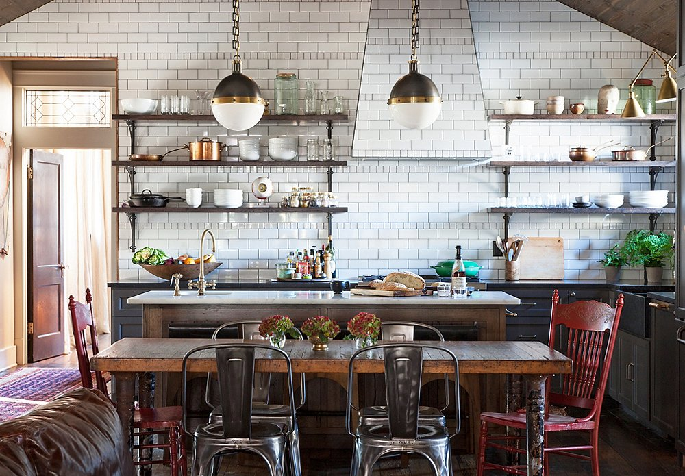 The eclectic mix of subway tile, vintage wooden dining table & chairs, metal chairs and shelves are very much Brooklyn interior design signatures