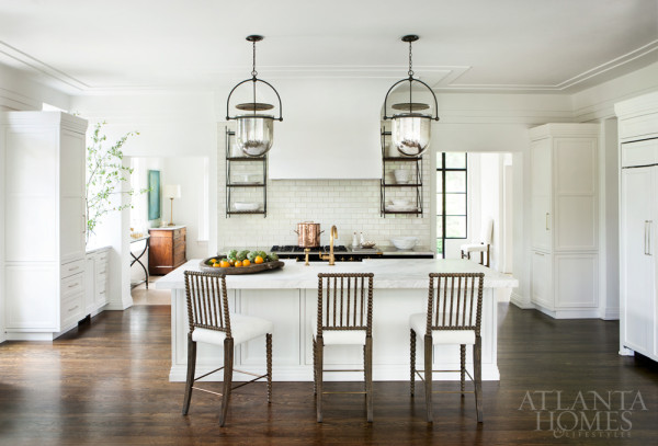 In the all-white kitchen simple lines and rich materials such as carrara marble, subway tiles, black metal finishes and rich wood flooring are paired for a clean crisp contrast