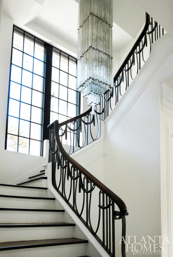 Black ornately detailed staircase and drop chandelier really stand out against the stark white walls