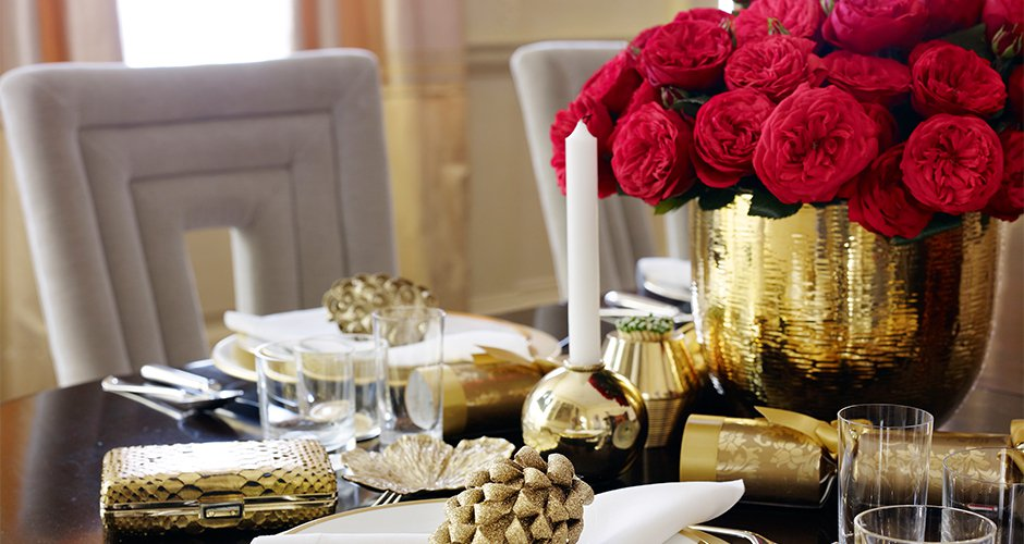 A holiday tablescape elegantly displayed in timeless, yet dynamic gold, red and white color scheme by Aerin Home Accessories