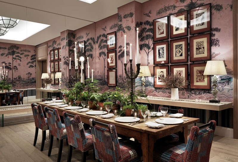 The dining room is wallpapered with oversized trees and plants making a great background for the artwork.  So, at first glance it all looks very busy but the elements that pull the room together are all the picture frames are black, the same size with same color combination matting in each. The terra-cotta matting is picked up in the dining chair fabric.  The bleached oak floors, dining table and console also bring the space together.  The large wrought iron candlesticks are an added dramatic touch in an already dramatic room.