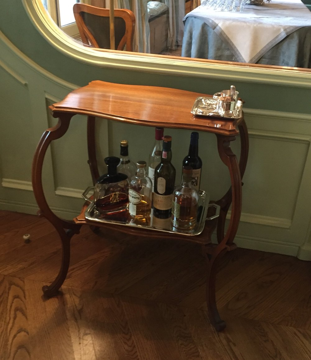 A beautifully carved side table does double duty as a bar cart