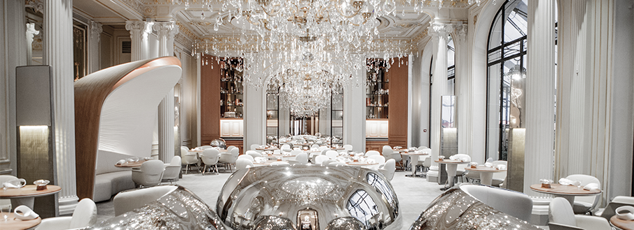 Alain Ducasse au Plaza Athénée is designed by Patrick Jouin and Sanjit Manku - there's plenty of sparkle from a trio of huge cascading crystal chandeliers hanging above sensuously curved seating, circular tables and banquettes -a Nordic palette of white and metallic finishes mixed with 12 ft high classic columns complete the grandeur of the room.
