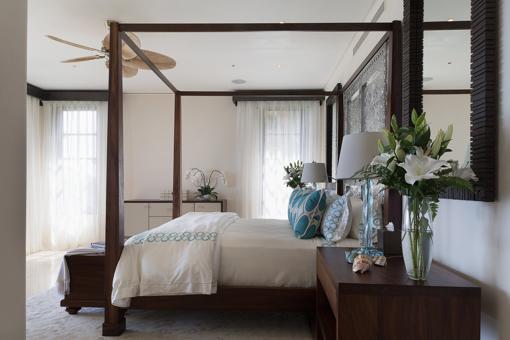An exquisitely hand crafted pair of silver doors from Oaxaca feature as the headboard in a bedroom of elegant simplicity