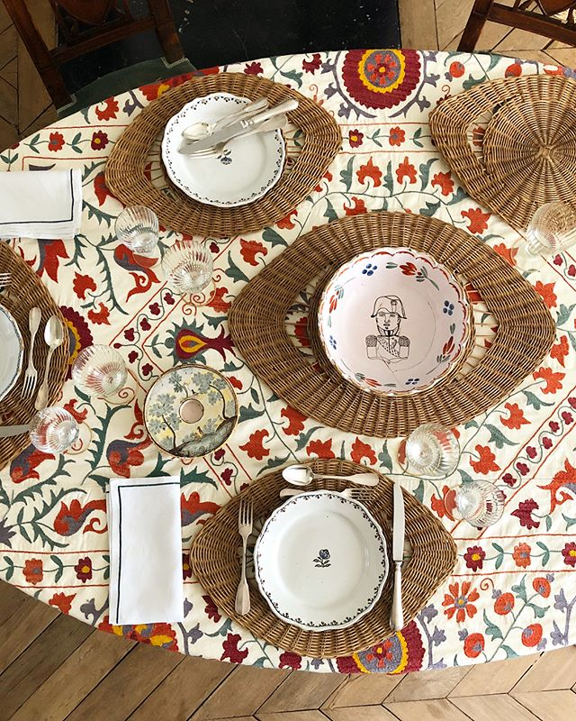 "Rattan ""eye"" placemats sit atop a vintage suzani tablecloth"