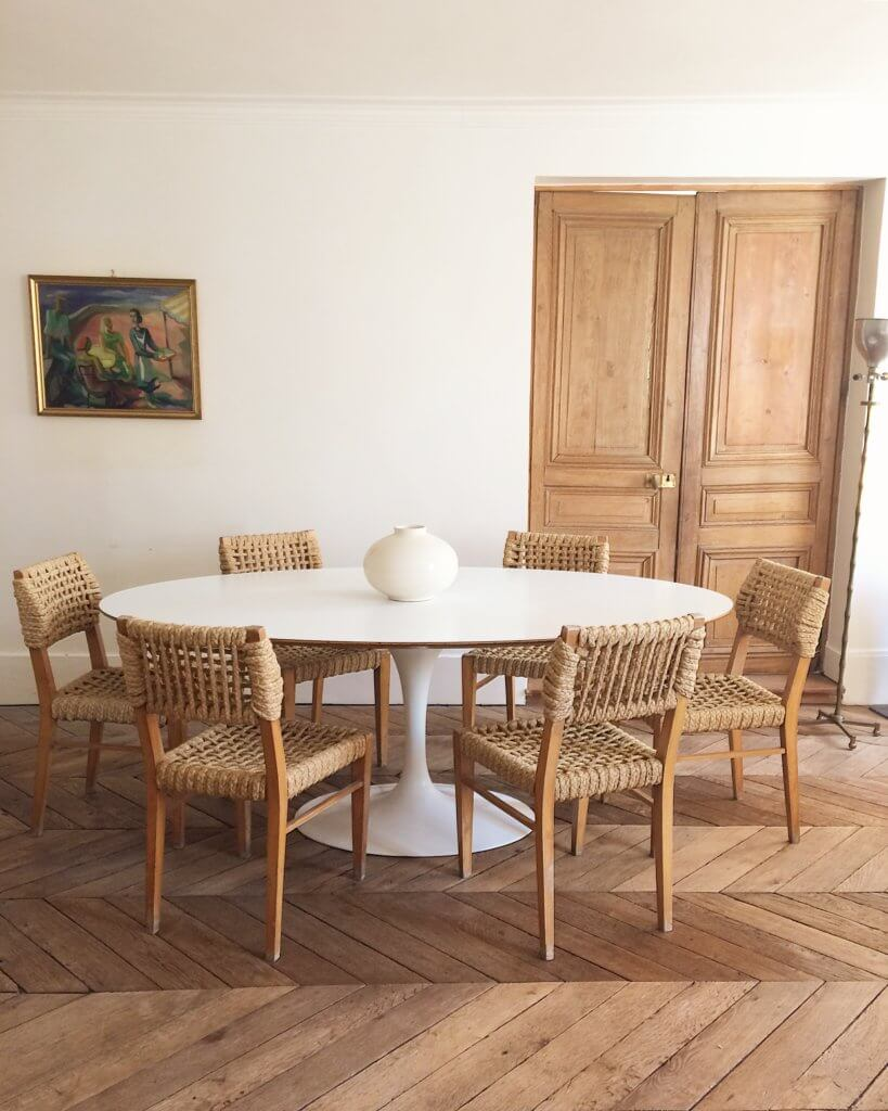 atelier-vime-saarinen-oval-dining-table-wood-floors-woven-chairs-white-walls-french-country.jpg