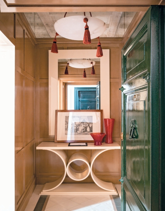 Layers of art, accessories and tassels dominate this vestibule framed by a super glossy door