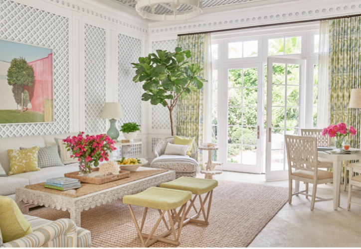 Classic Palm Beach decorative elements in the living room include trellis lined walls, sisal rug, bamboo and wicker furniture in a green, pink and white color palette reminiscent of Lilly Pullitzer