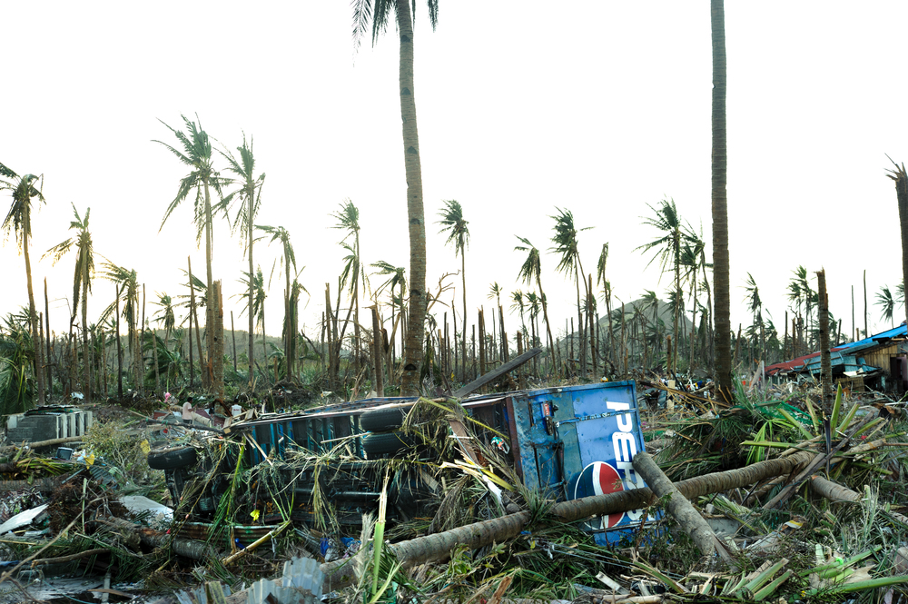 """On the road into Tanauan, a Pepsi truck lies overturned. A day later and still without food or fresh water, local residents enter the truck to find crates of unopened Pepsi bottles, which they share amongst the local population and the medical team. Some media outlets characterize this behavior as """"looting"""", further discouraging relief organizations from extending their reach beyond the safety of Tacloban airport 15 miles to the north."""