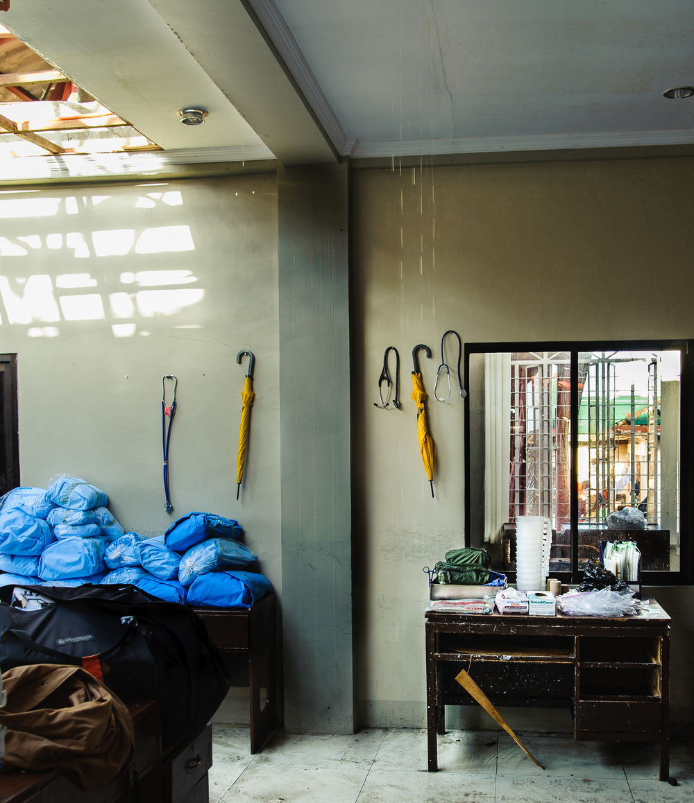 Water pours down the walls and through the roof of the team's makeshift OR, where stethoscopes and umbrellas share equal prominence in the care of patients.