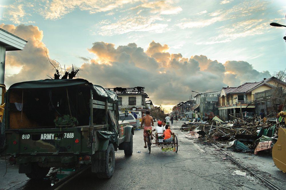The sun rises over the town's recently cleared main street, where a bike taxi ferries passengers day 4 status post typhoon landfall.