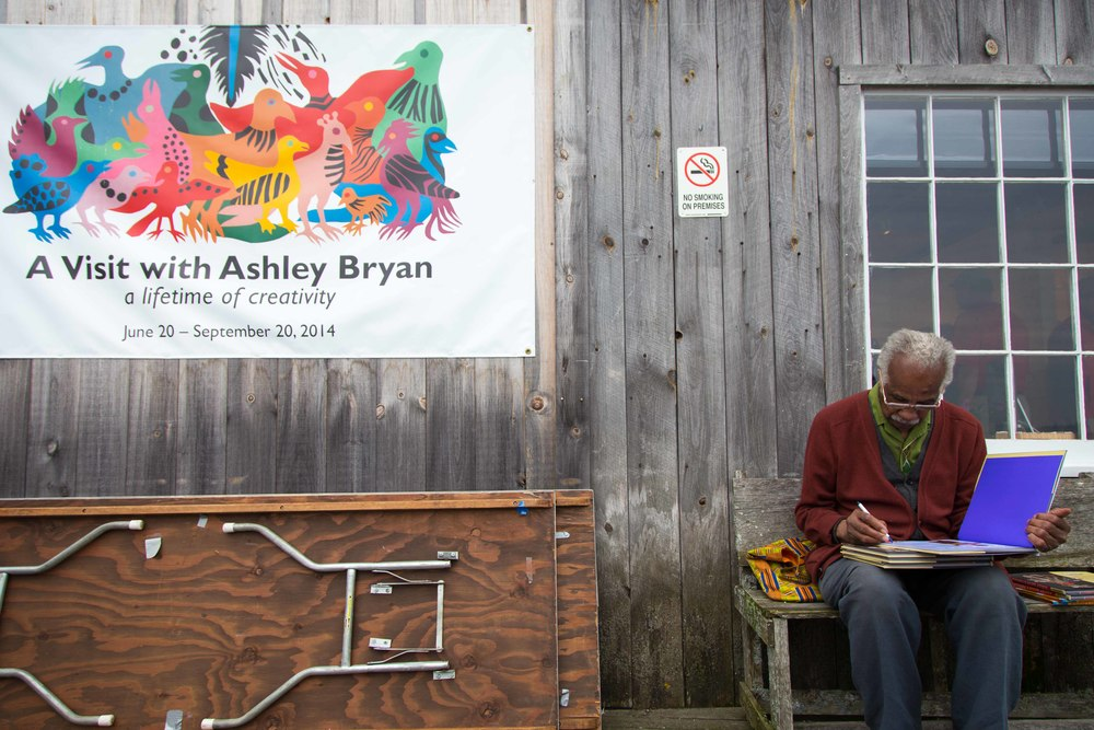 Ashley Bryan takes advantage of a quiet moment on the dock to autograph copies of his latest book.