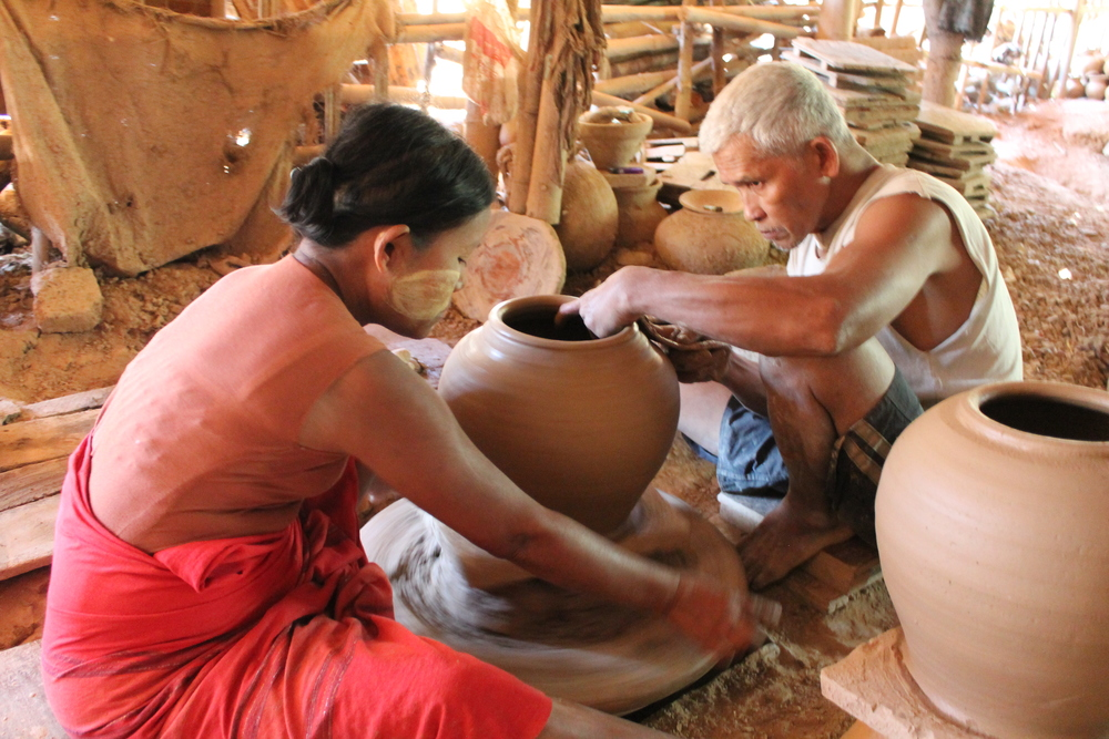 throwing a vase on a hand wheel, he is using a circular sliced bamboo as a tool